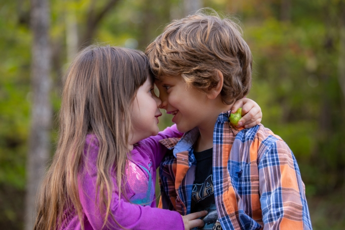 girl and boy pressing noses together in photograph