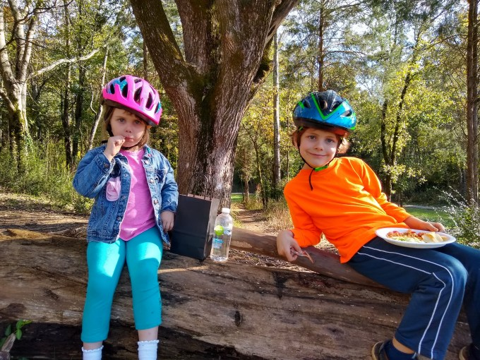 kids in bike helmets resting on log at Baker's Creek Preserve